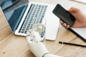 close-up view of person using smartphone and hand of robot holding glass of water