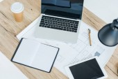 pohled z vysokého úhlu notebook, digitální tabletu, notebooku a plán na dřevěný stůl