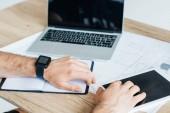 Oříznout záběr osoby nošení hodinek smartwatch a používání digitálních tabletu na pracovišti