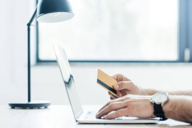 cropped shot of person holding credit card and using laptop at workplace