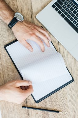 partial top view of person holding blank notebook at workplace