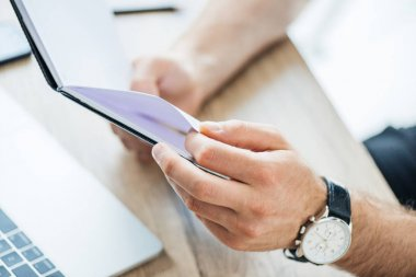 close-up partial view of male hands holding notebook at workplace