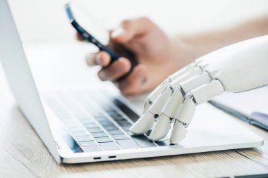 close-up view of human and robot hands using smartphone and laptop at wooden table