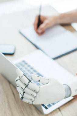 close-up view of robotic arm using laptop and human hand taking notes at workplace