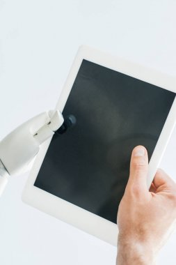 close-up view of human hand and robotic arm holding digital tablet with blank screen isolated on white