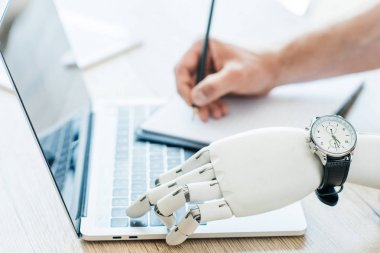 close-up view of robotic arm with wristwatch using laptop and human hand taking notes at wooden table