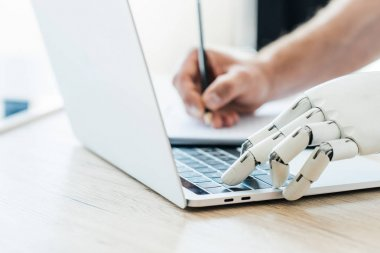 close-up view of robotic arm using laptop and human hand taking notes at wooden table