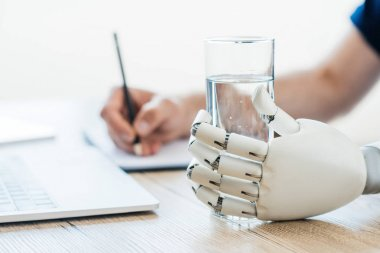 selective focus of robotic arm holding glass of water and person taking notes at wooden table