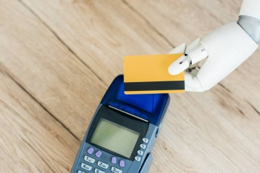 top view of robot holding credit card above payment terminal on wooden table