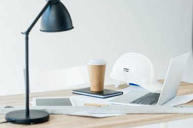lamp, digital tablet, laptop, hard hat and disposable coffee cup on table
