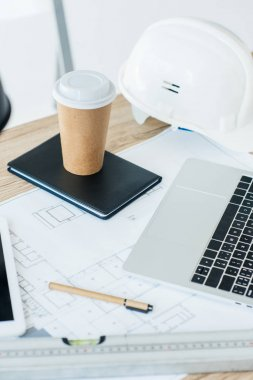 laptop, blueprint, notebook, disposable coffee cup and hard hat at workplace