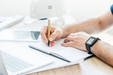 partial view of person wearing smartwatch and taking notes at workplace