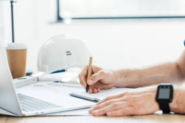 cropped shot of person wearing smartwatch and taking notes at workplace