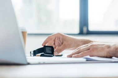 cropped shot of person holding smartwatch and using laptop at workplace