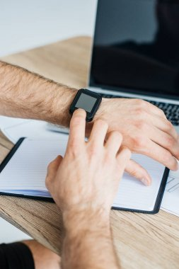 close-up partial view of person using smartwatch at workplace