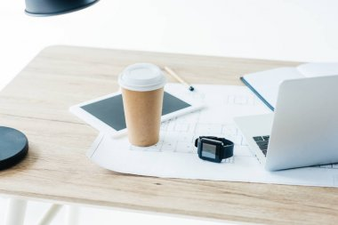 disposable coffee cup, digital tablet, smartwatch, laptop and blueprint on wooden table