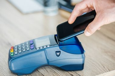 Cropped shot of person using smartphone and payment terminal stock vector