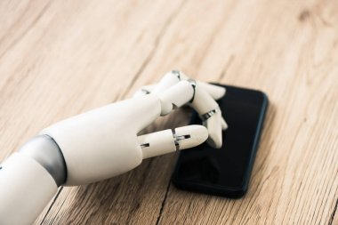 close-up view of robot using smartphone on wooden table
