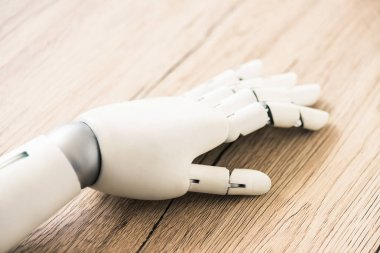 close-up view of hand of robot on wooden surface