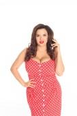 Fotografie krásná a navíc velikost žena v červené tečkované šaty při pohledu na fotoaparát izolované na bílém