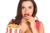 Fotografie šokoval plus velikost ženy jíst popcorn a při pohledu na fotoaparát izolované na bílém