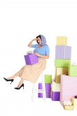 Photo full length view of pin up woman holding gift box and sitting on stool near piles of presents isolated on white