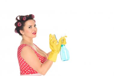 side view of plus size woman in rubber gloves with cleaning supplies isolated on white
