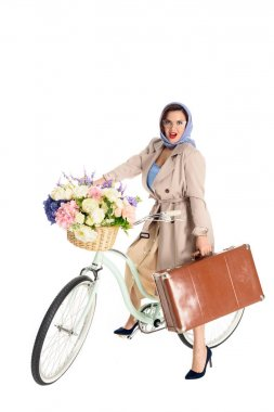 beautiful pin up woman sitting on bicycle and holding suitcase isolated on white
