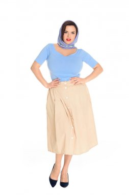 full length view of stylish plus size pin up model standing with hands on waist and looking at camera isolated on white