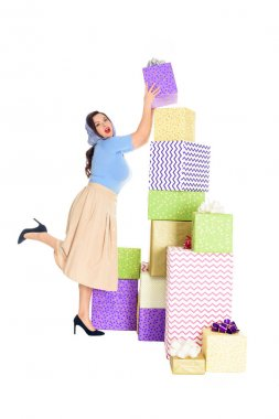 full length view of stylish young woman looking at camera while standing near pile of gift boxes isolated on white