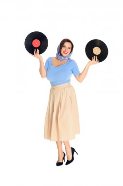 full length view of beautiful size plus pin up woman holding vinyl records and smiling at camera isolated on white