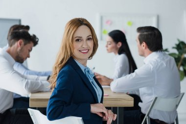 selective focus of smiling businesswoman and colleagues at workplace in office