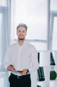 Fotografie portrét usmívající se podnikatel v oblasti formálního oblečení s Poznámkový blok v úřadu