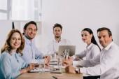 Selektivní fokus úsměvu se spolupracovníky na pracovišti s dokumenty v kanceláři