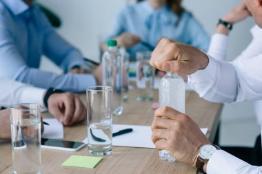 cropped shot of businessman opening bottle of water with colleagues at workplace near by  in office