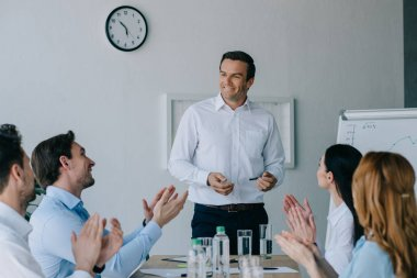 business coworkers applauding to smiling mentor while having business training in office