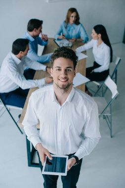 selective focus of smiling businessman and coworkers at workplace in office