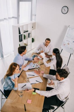 high angle view of business colleagues discussing business idea at workplace in office
