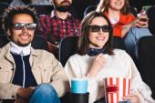 Selektiver Fokus multiethnischer Freunde in 3D-Brillen, die lächeln und Filme im Kino ansehen