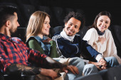 Fotografie selective focus of multicultural friends smiling and talking in cinema