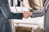 oříznutý pohled na podnikatele, jak si potřásají rukama ve skladu