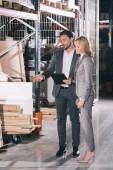 jóképű üzletember ujjal mutogat az építőanyagokra, miközben üzletasszony közelében áll