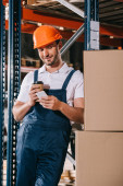Photo smiling loader holding coffee to go and using smartphone in warehouse