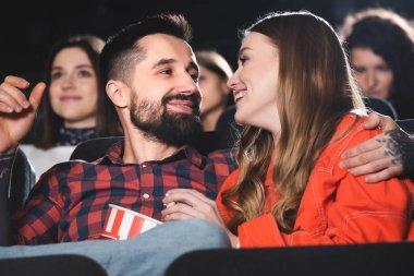 Handsome boyfriend hugging smiling and attractive girlfriend in cinema stock vector