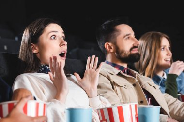 Selective focus of shocked woman watching movie with friends in cinema stock vector