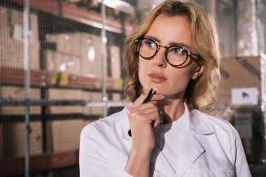 thoughtful storekeeper in glasses looking away while holding pen in warehouse