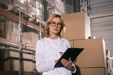 serious storekeeper looking at camera while writing on clipboard in warehouse