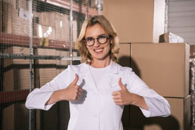 cheerful storekeeper in glasses showing thumbs up and looking at camera