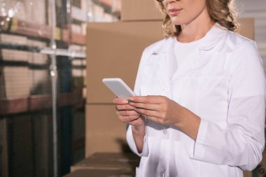 cropped view of storekeeper in white coat using smartphone in warehouse