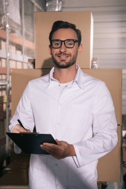 handsome storekeeper in glasses smiling at camera while writing on clipboard